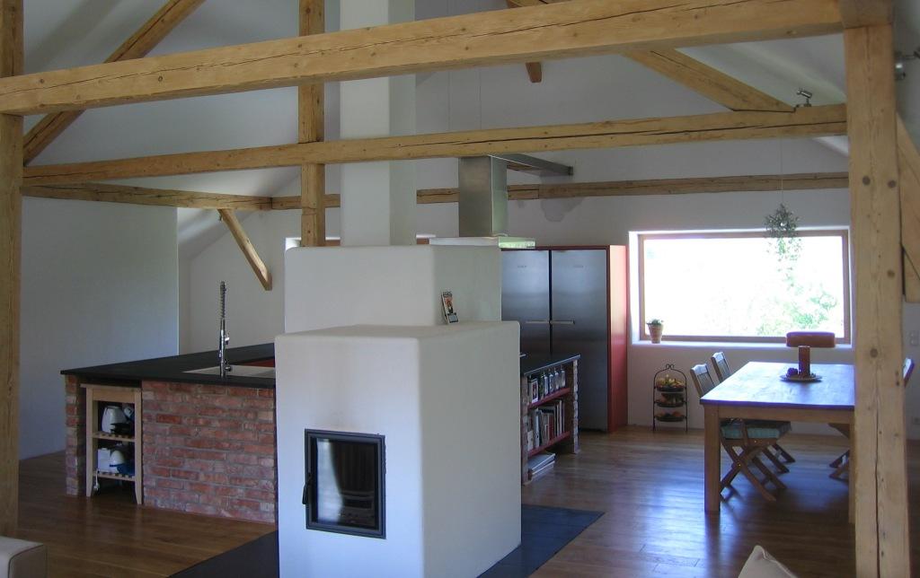 Die Küche ist in das Gesamtkonzept eingebettet - der Ziegel ist dem Abbruch entliehen - Arbeitsplatte aus Granit und die Sonne scheint